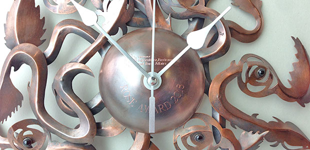 Close-up image of Climbing Roses Clock |  Copper, clock mechanism and garnets | Diameter 27 cm x Height 5 cm | Copper was etched, scored and foldformed. The garnets were bezel set in Sterling silver | Photo credit Leanne McCormack.